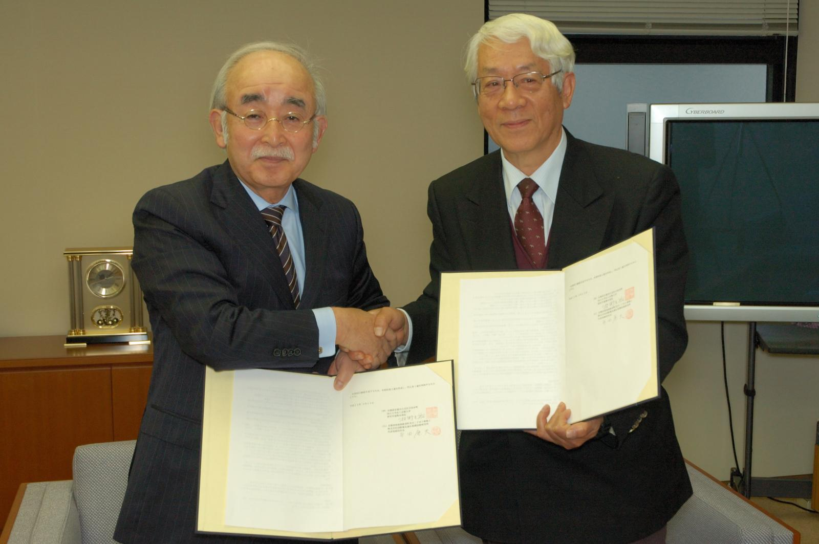 ATRの平田康夫代表取締役社長(右)と京都大学産官学連携本部の牧野圭祐本部長